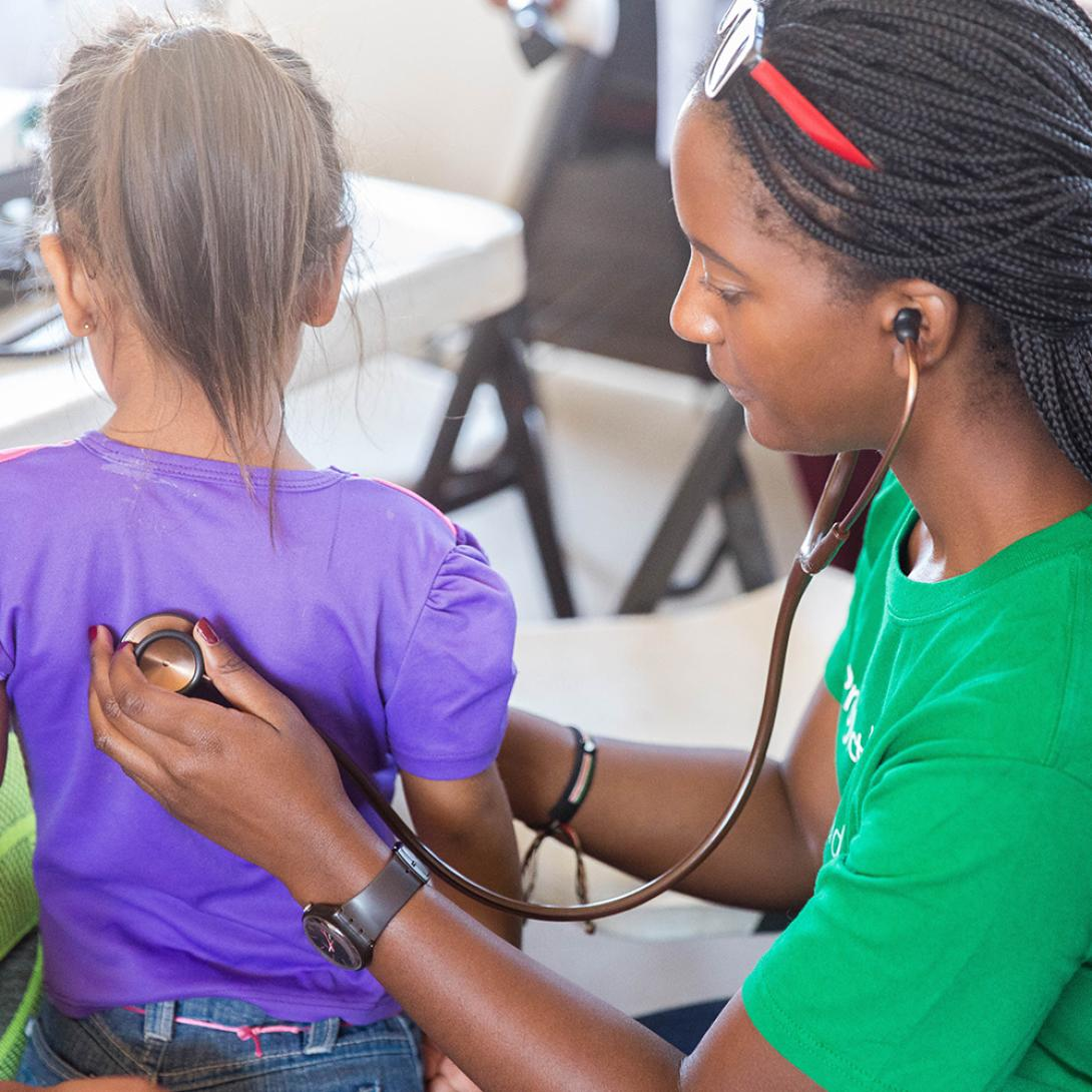 Medical intern measures the heart rate of a young girl in Mexico.